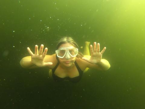 Photo of Anna Swanson in goggles swimming underwater